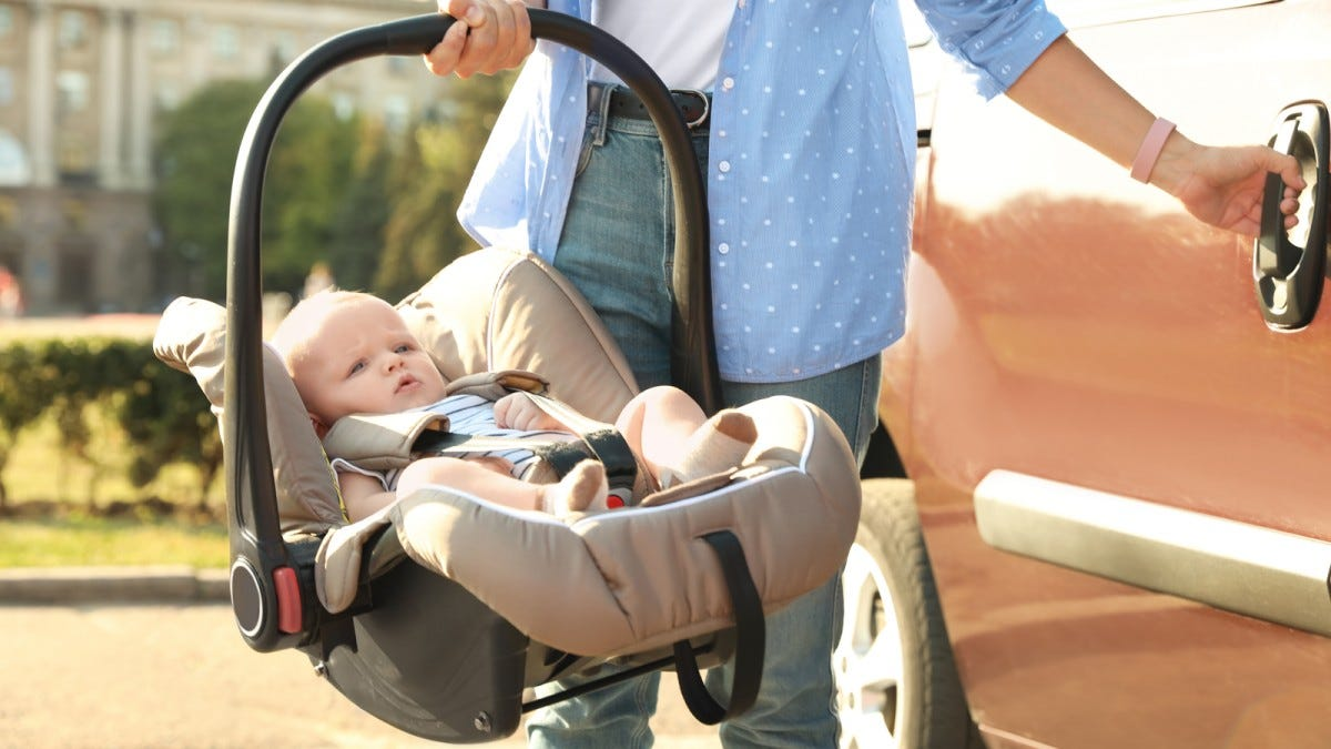 A mother's hand holding a baby in an infant car seat with one hand, and opening a car door with the other.