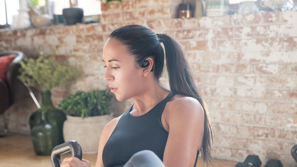 A woman exercising while wearing Bose Sports Open Earbuds