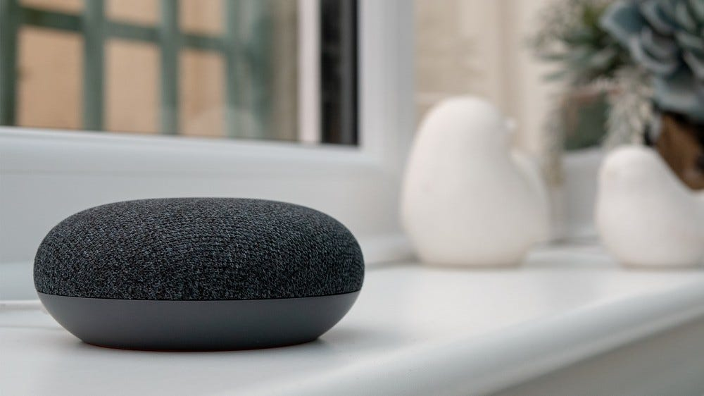 A photo of a Google Nest Mini on a countertop.