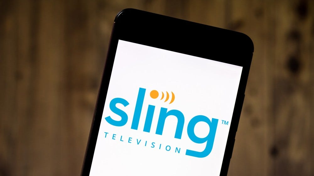 SLING TV logo displayed on a smartphone in front of a wooden background