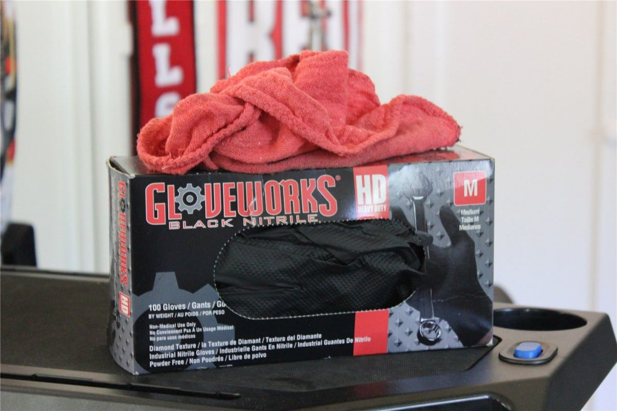 A red shop rag lying on top of a box of Gloveworks Black Nitrile Gloves.