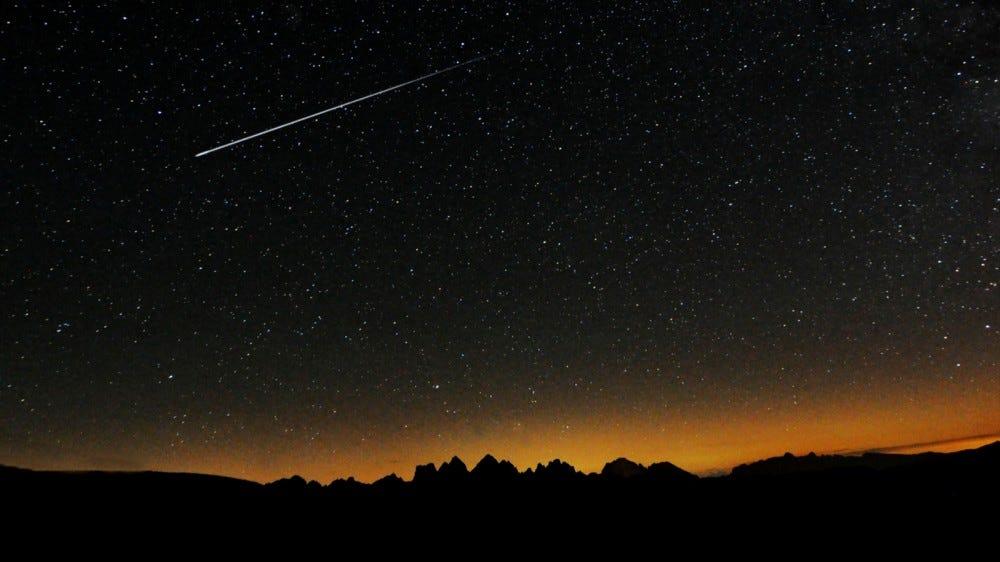 Звезды в ночном небе над горным силуэтом с метеоритным дождем