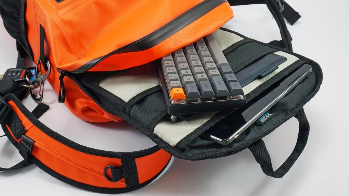 The Booē Hybrid 20 backpack, unzipped, with a keyboard and tablet inside.