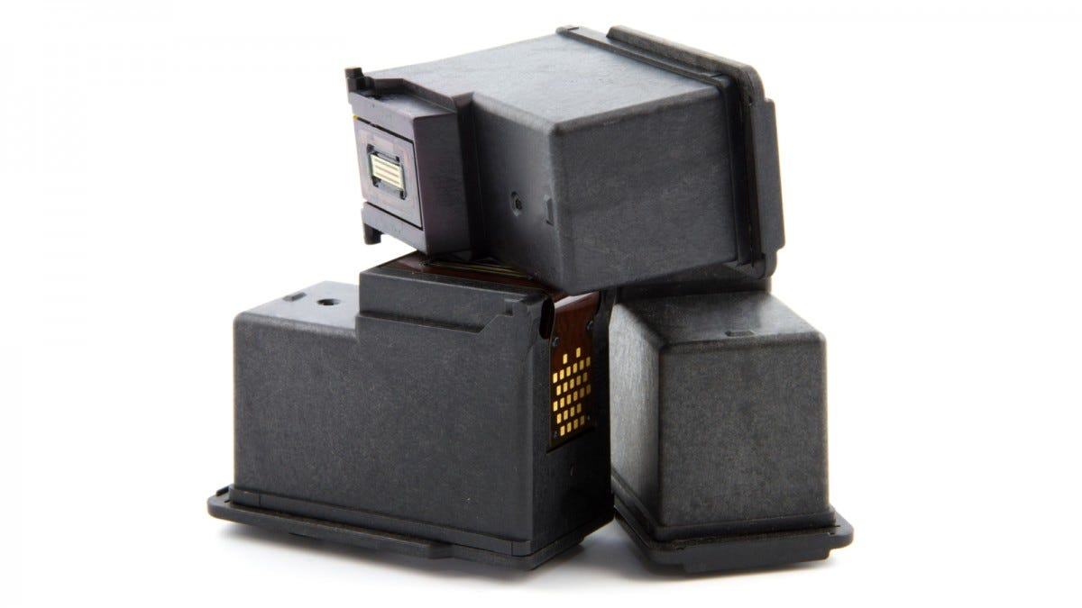 One printer cartridge lying on top of two others.