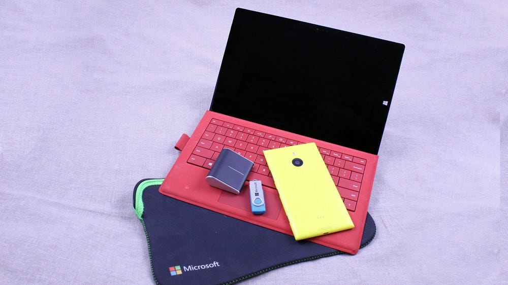 A Microsoft Surface Pro 3, yellow Windows phone, Surface Mouse, and branded case and phone.