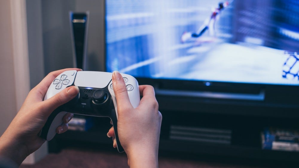 Close-up of person playing with on a PlayStation 5.