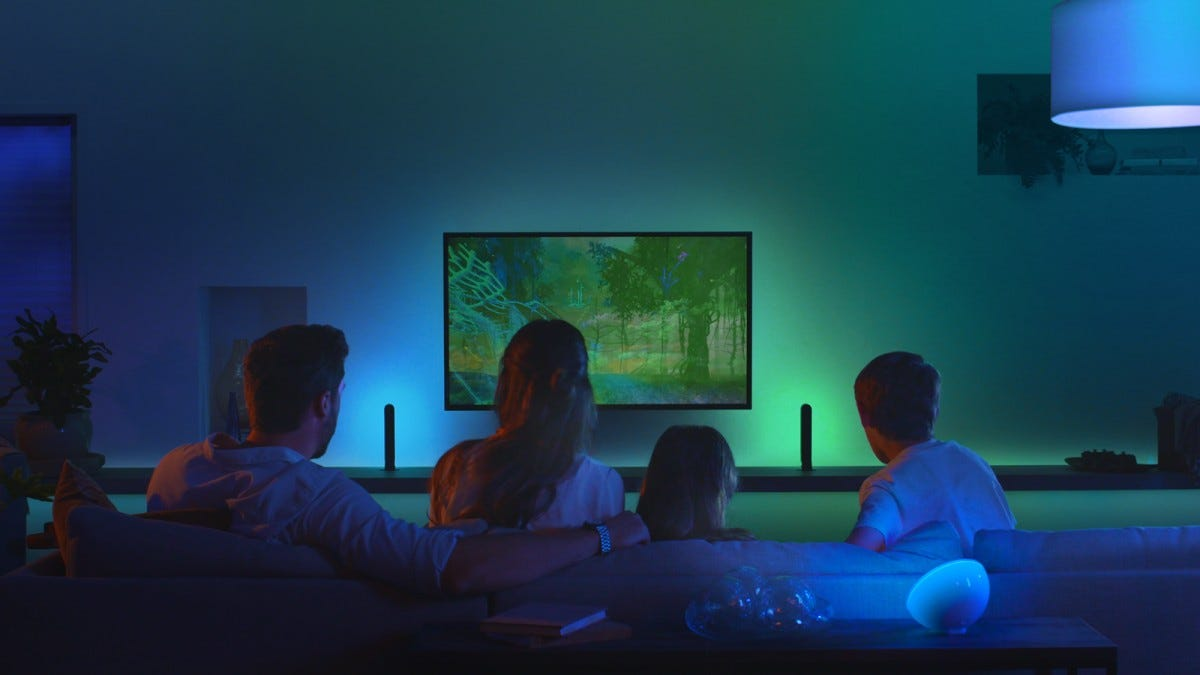 A family in a living room, surrounded by Philips hue lights.