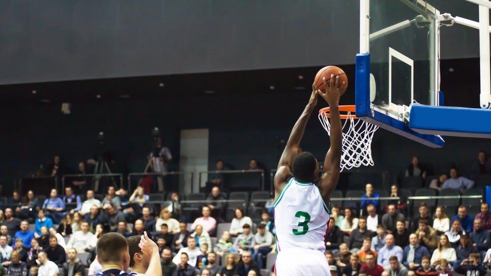 An NBA Player dunking a basketball.