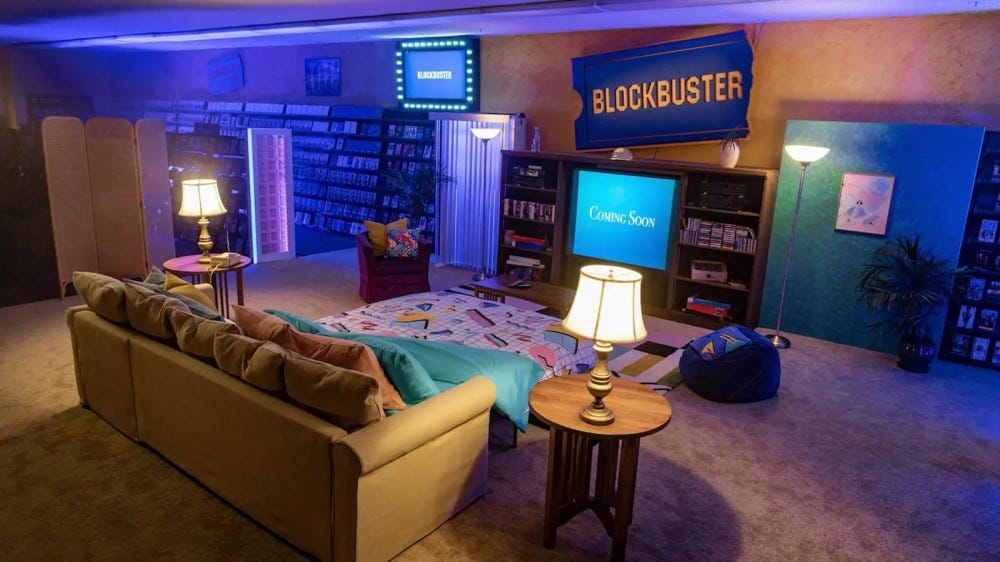 A living room setup inside a Blockbuster store.
