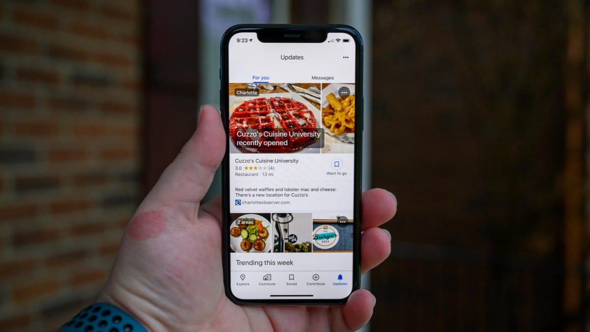 An iPhone with the new Google Maps Updates tab showing a newly opened local restaurant.
