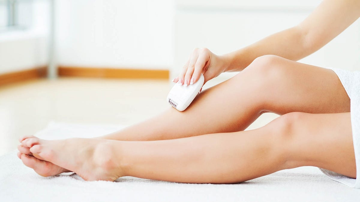 woman removing hair from her legs using an epilator