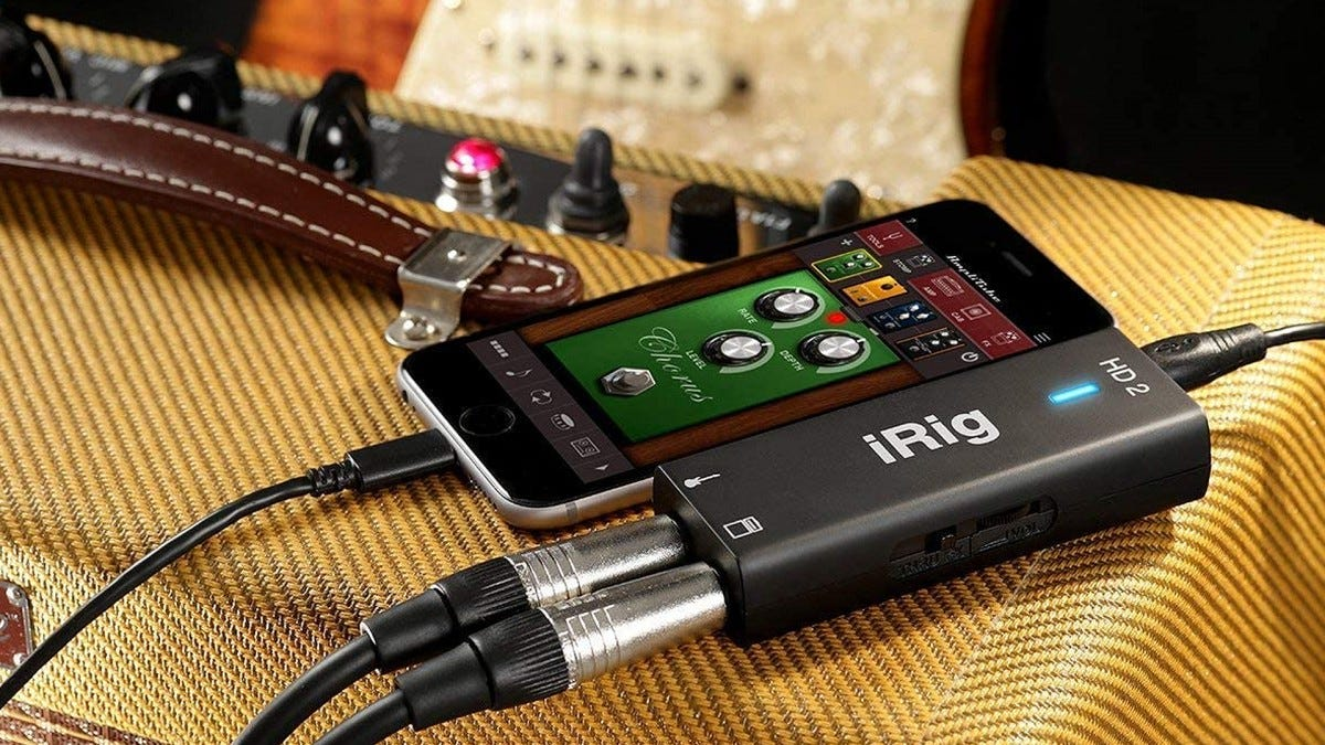 A photo of the iRig, an iPhone, and a guitar.