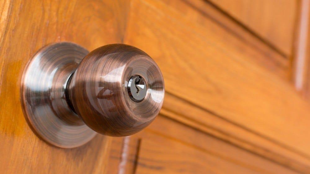 A brass doorknob on a wooden door.
