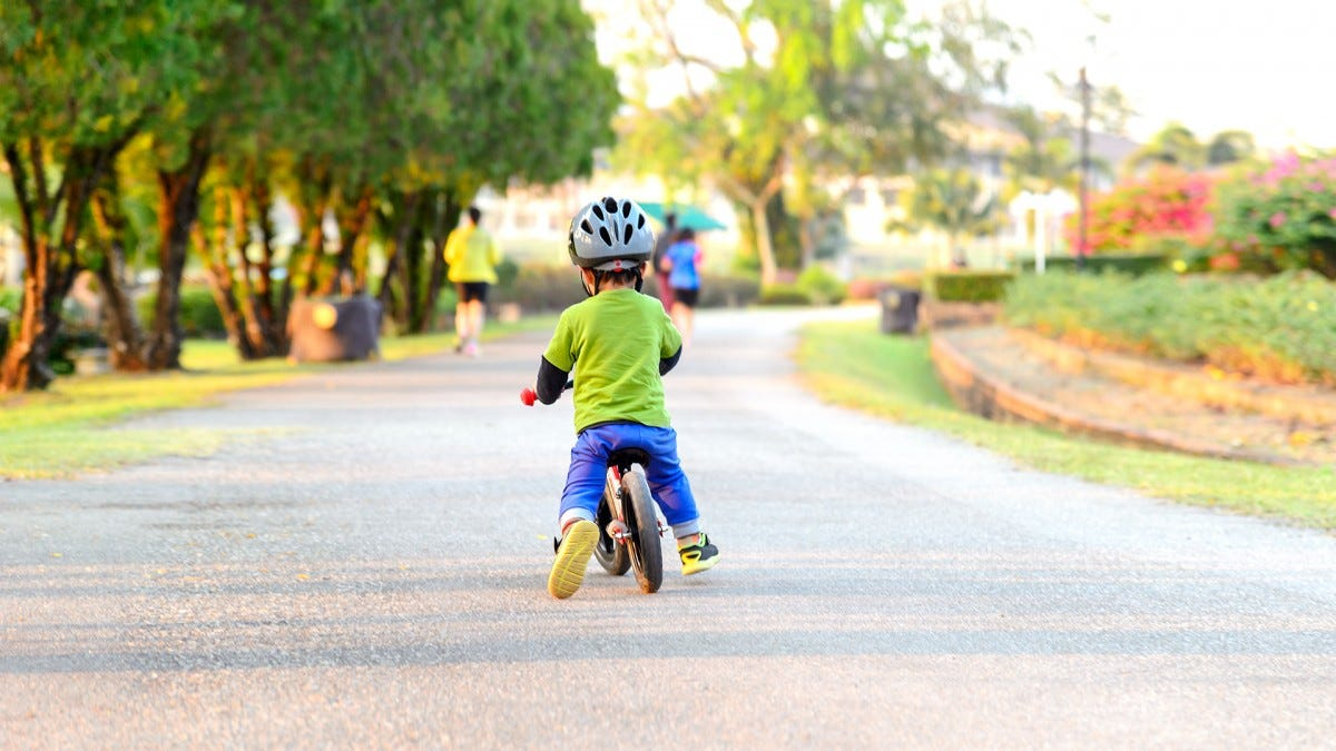 A toddler gliding on a balance bike.
