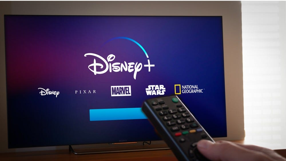 Hand holding a remote control with the new Disney+ loading screen on TV