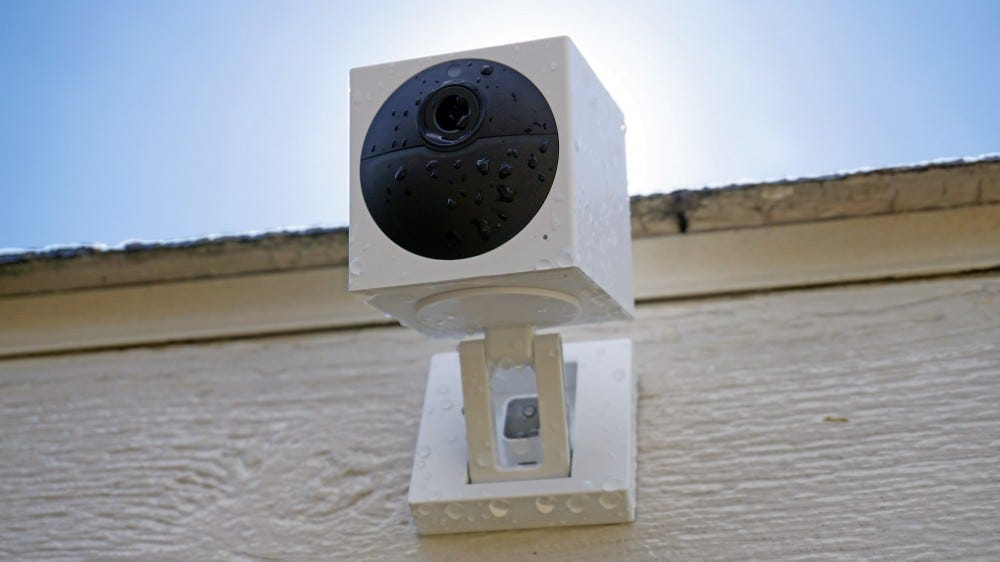 Wyze Cam Outdoor, mounted to the wall, covered in drops of water