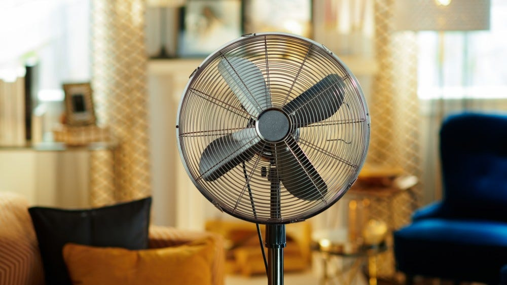 Closeup on electric floor standing fan ni a modern living room in sunny hot summer day