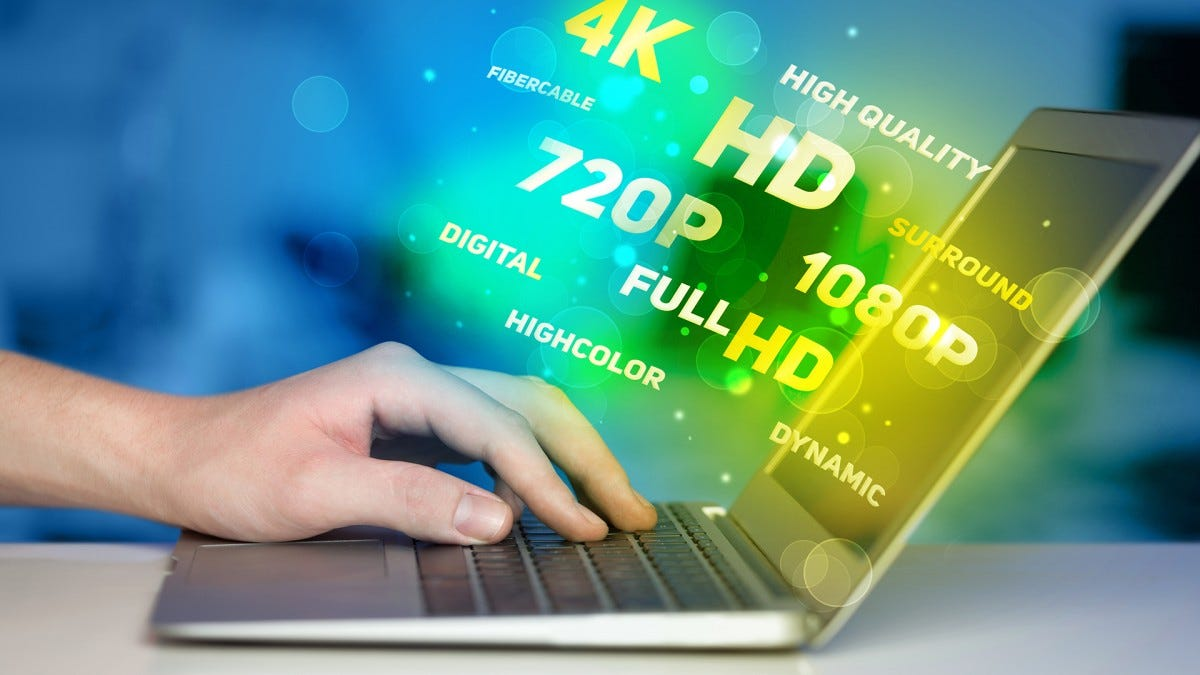 """A man's hand on a laptop keyboard as words like """"4K,"""" and """"HD"""" float out of the screen."""