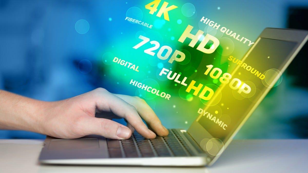 """La mano di un uomo sulla tastiera di un laptop mentre parole come """"4K"""" e """"HD"""" fluttuano fuori dallo schermo."""