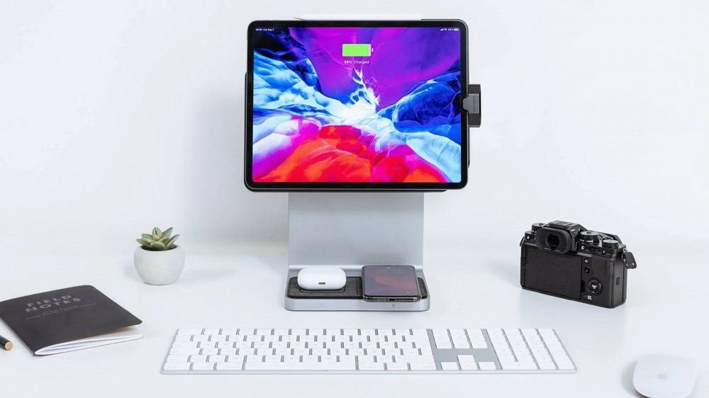 An iPad docked to an iMac looking stand, while wireless charging an iPhone and AirPods