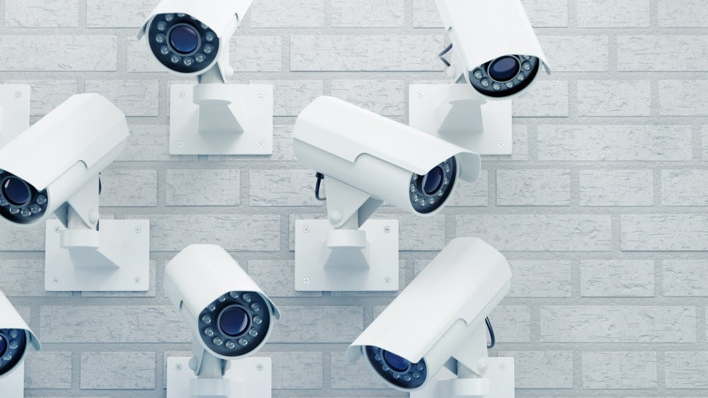 Group of external surveillance cameras mounted on a brick wall.