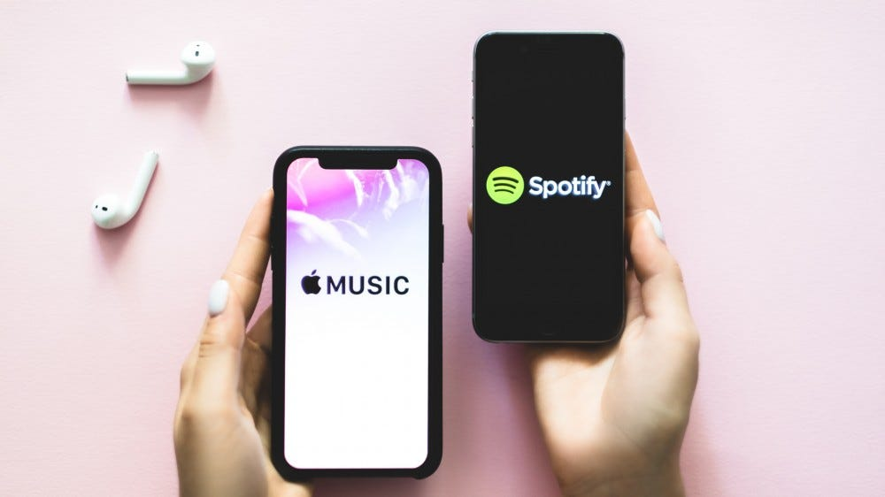hands holding iPhone X with Apple Music app and another with Spotify music streaming services