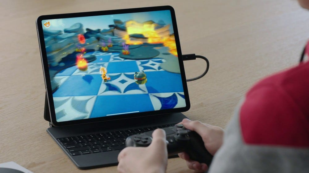 A gamer using a DualShock 4 controller with the iPad Pro.