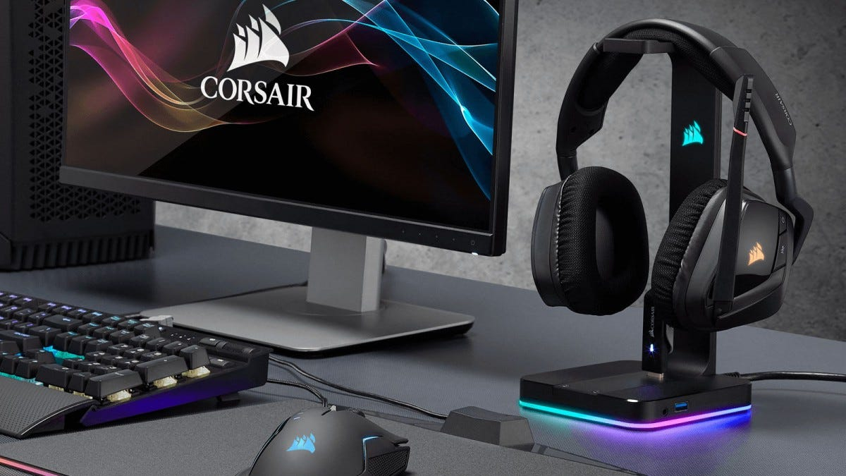 computer desk with headphones sitting on a headphone stand