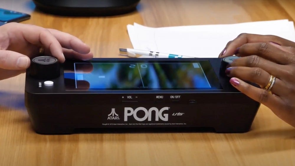 Arcade1Up Mini Pong machine played by two people on a table