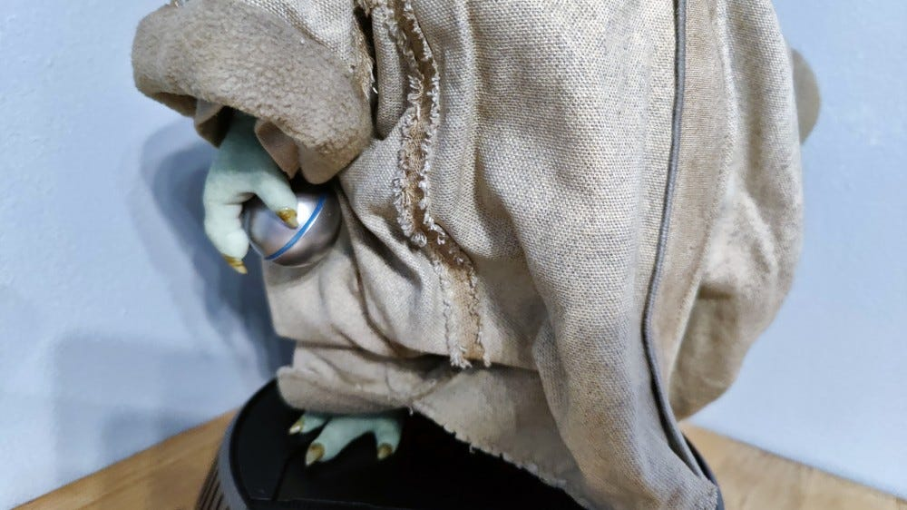 A closeup of Baby Yoda's hand, holding a round shift knob.