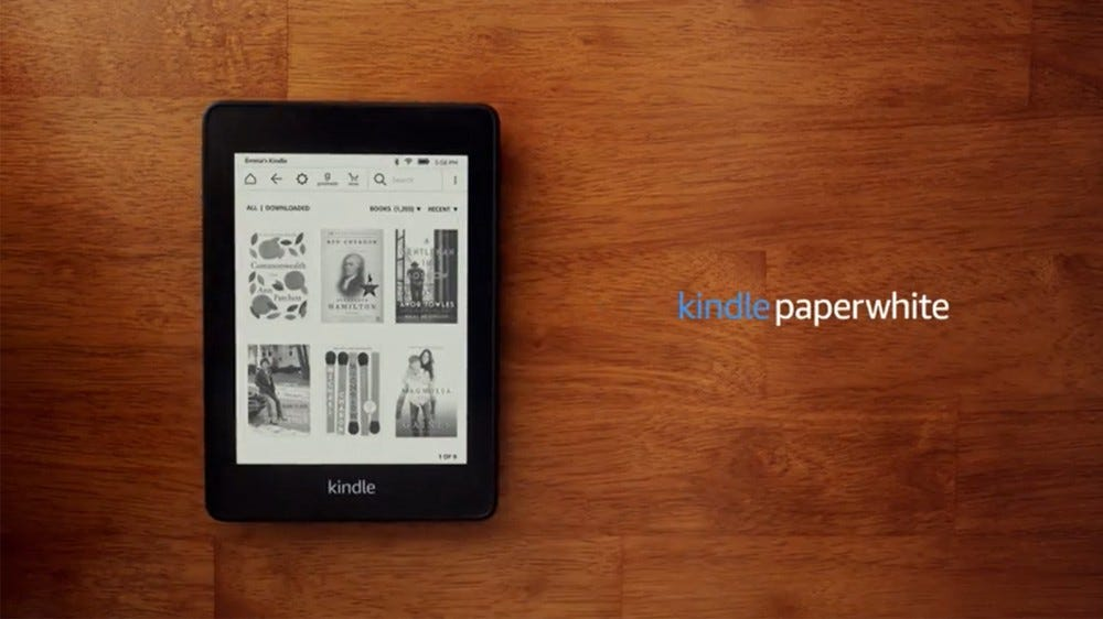 Kindle Paperwhite showing book selections while laying on a wooden surface