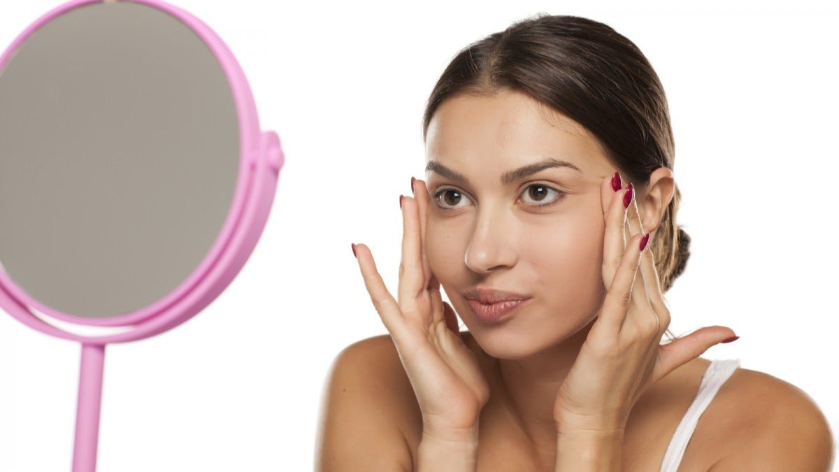 A young woman applying makeup primer