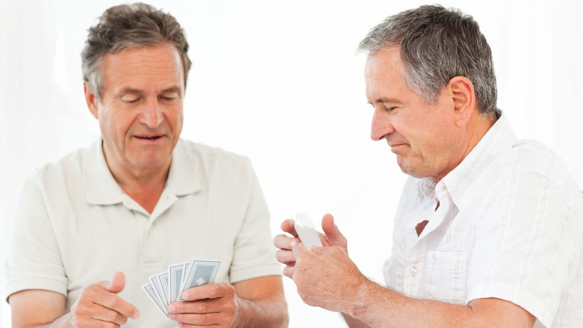 An older couple playing a card-based board game