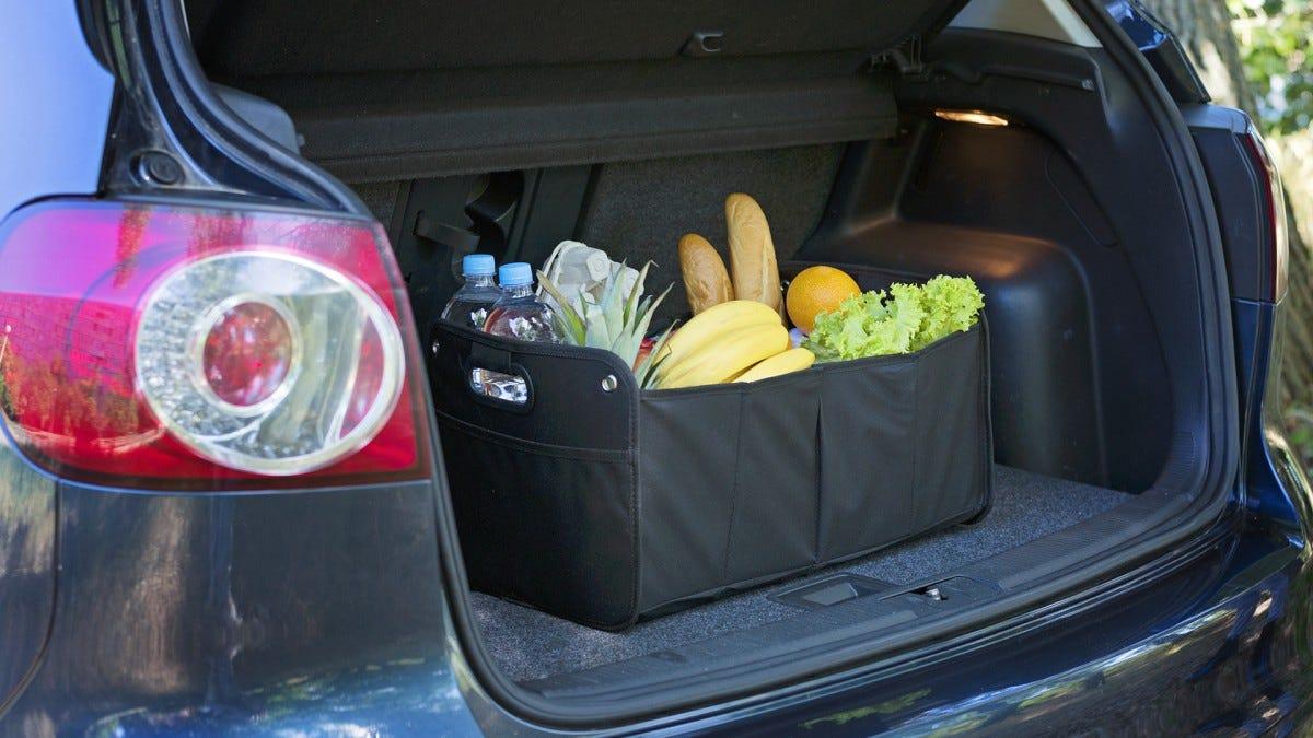 A black trunk organizer full of groceries in a trunk.