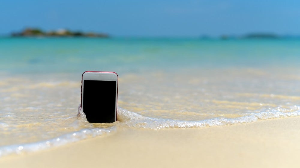 Smartphone stuck in sand with light waves crashing over it