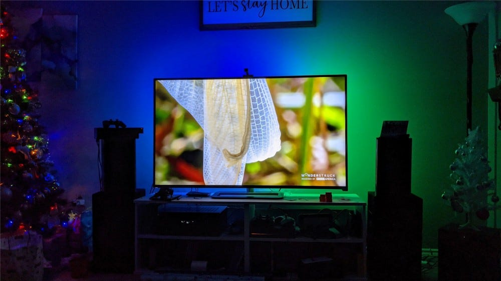 A dark room with the Immersion lighting up a wall behind a TV