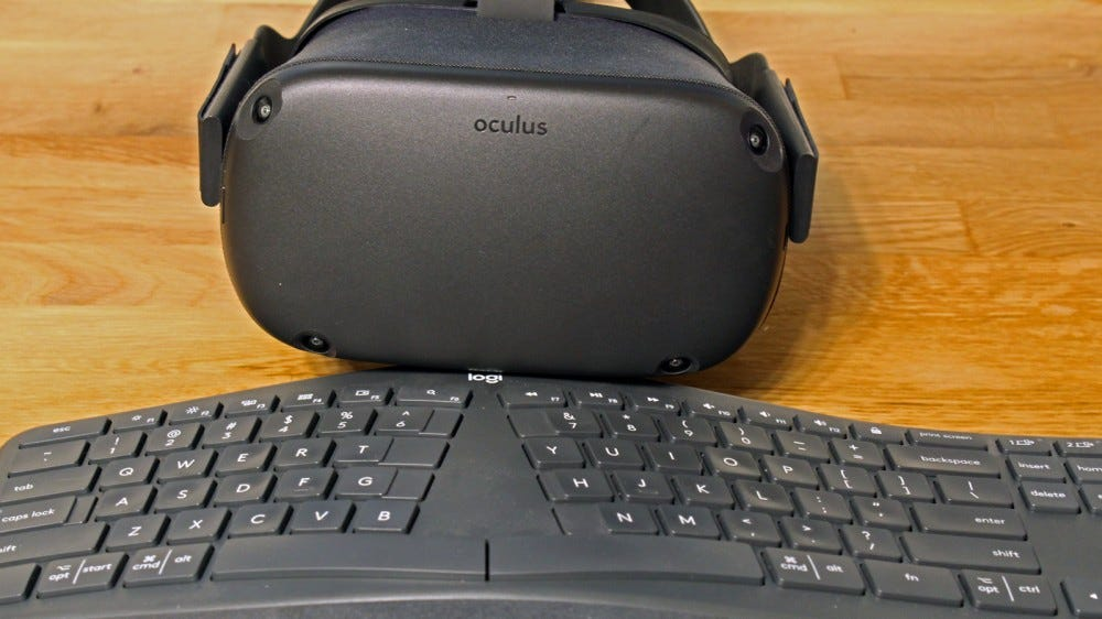 An Oculus Quest in front of a Logitech keyboard