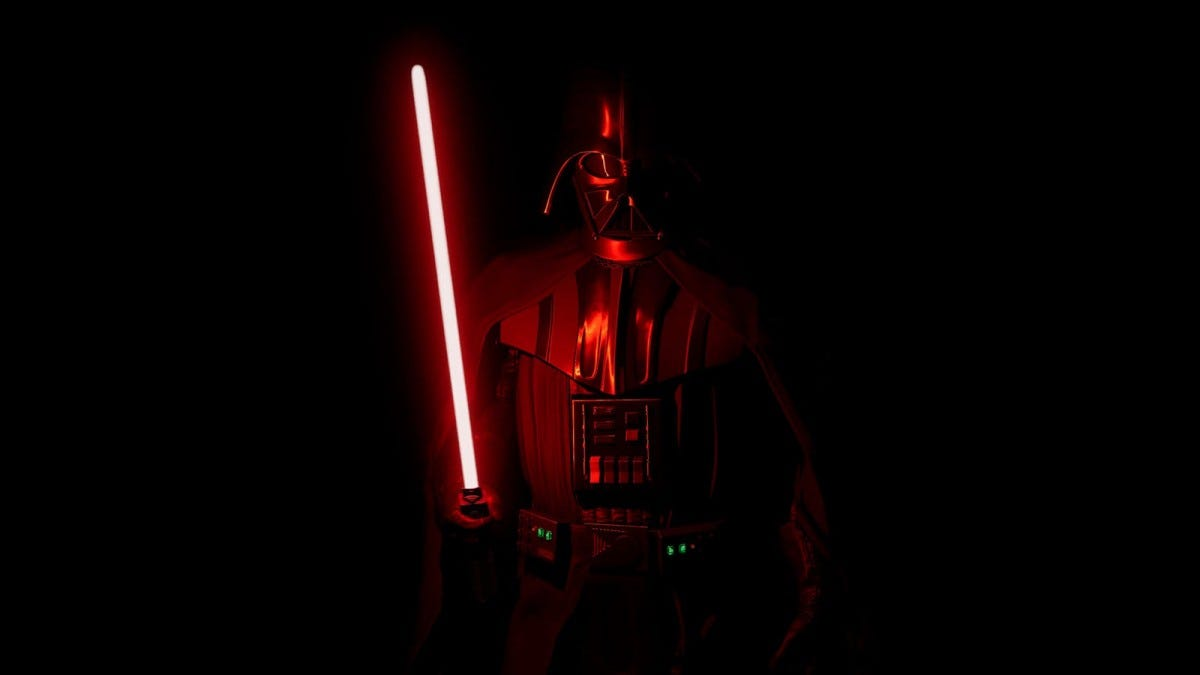 Darth Vader, standing in a pitch black room illuminated by a red lightsaber.