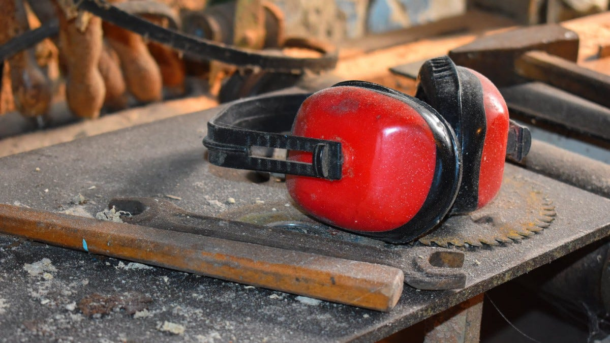 A red set of noise isolating ear muffs on a workbench.