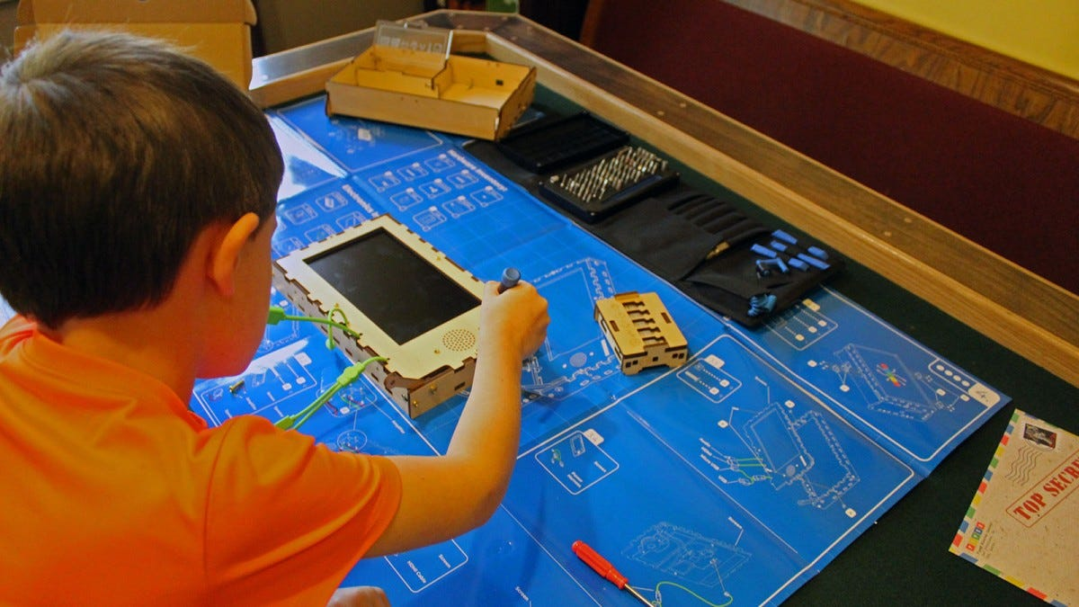 A young boy building a monitor component to the Piper Computer.