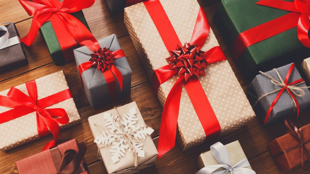 Lots of gift boxes on wood background, wrapped in craft and colored paper decorated with red ribbon bows and snowflakes