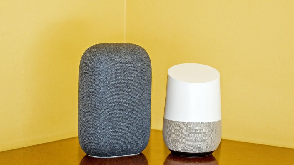 A Nest Audio next to a Google Home, showing it is skinner and taller than the Home.