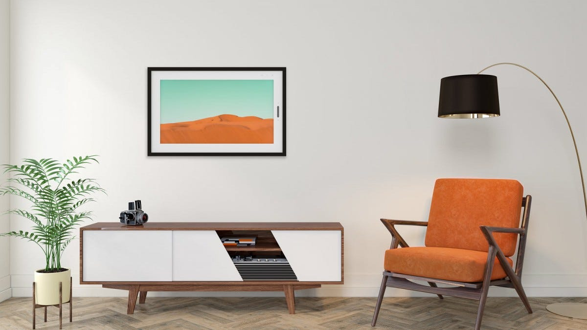 A Lenovo Smart Frame displaying a desert scene, hung over a modern tv stand.