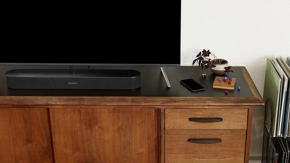 Sonos Beam Soundbar on an entertainment stand with a TV and other decor