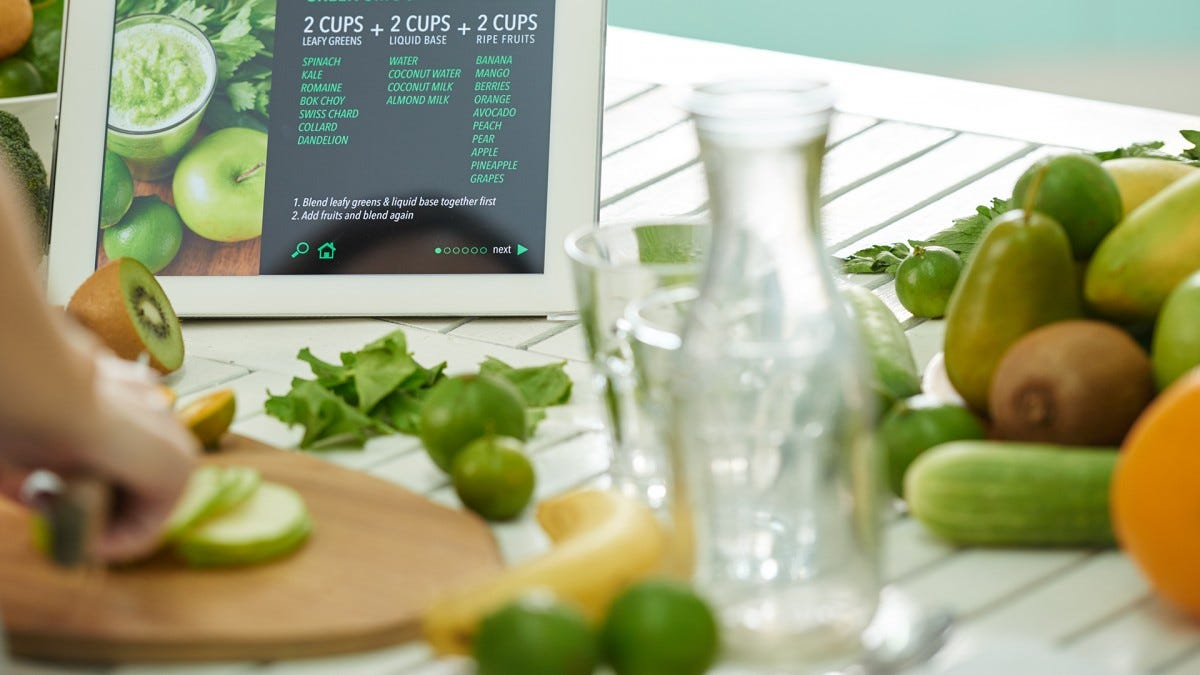 a person prepares a fresh meal on a counter filled with fruits, vegetables, and a tablet displaying a recipe