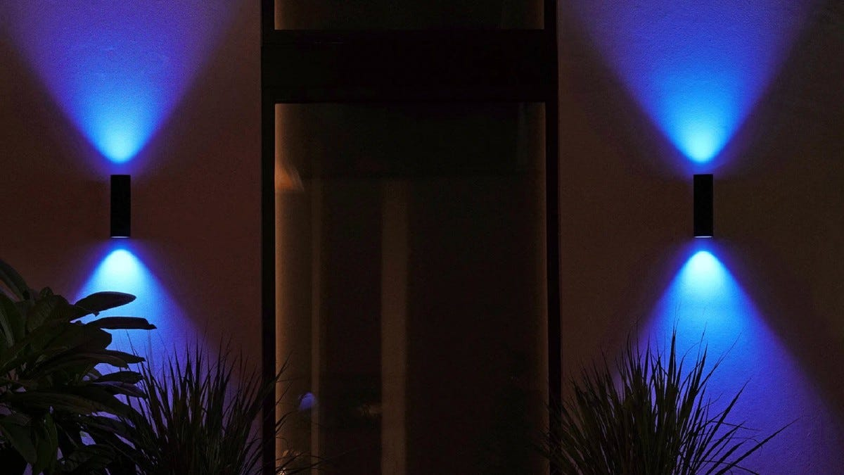 Two wall mounted lights shining blue light up and down vertically.