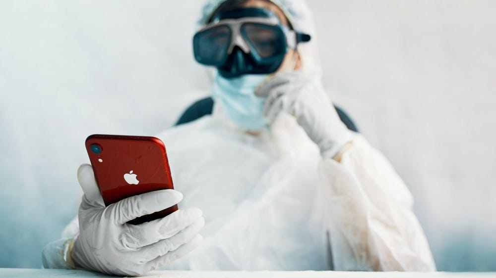 A person in a biohazard suit trying to unlock their iPhone.