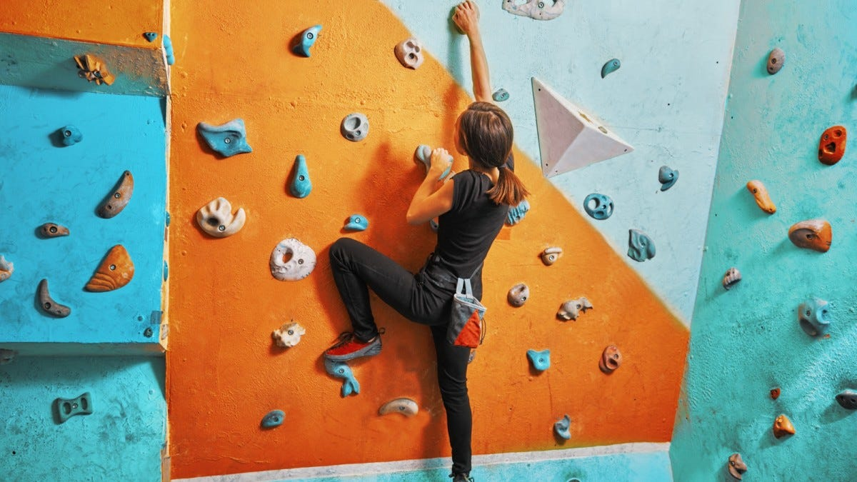 Young woman indoor climbing.