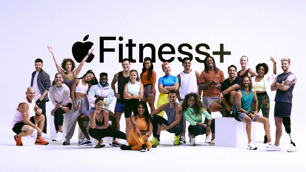 A large group of training coaches stand in front of the Apple Fitness + logo