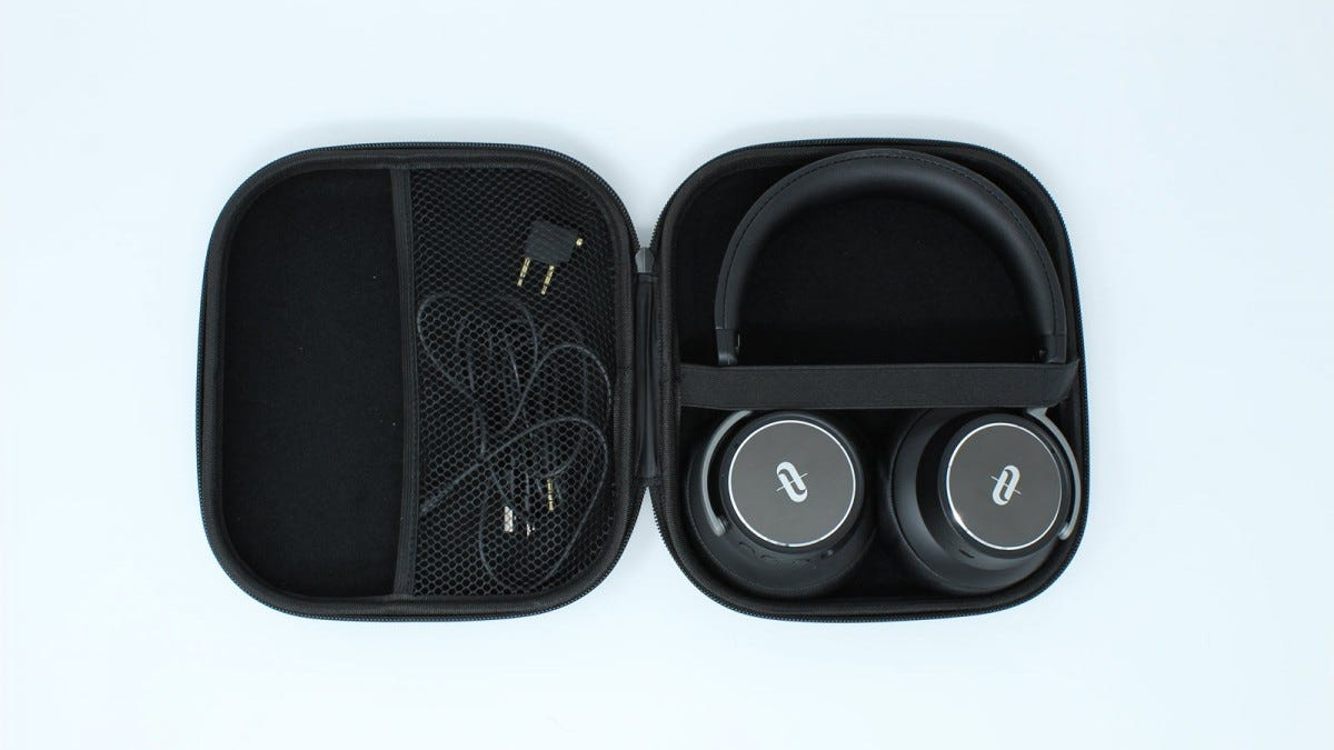 The headphones inside the case, along with microUSB cord, headphone jack cord, and airplane adapter.